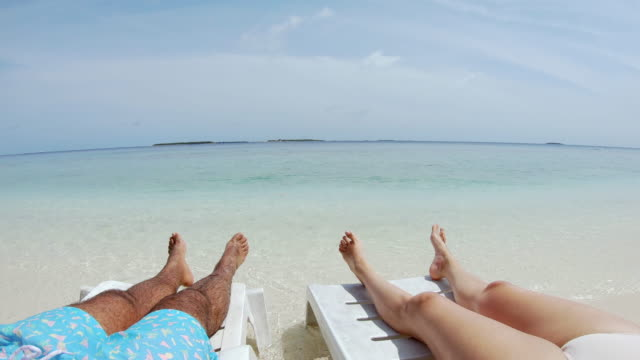 Young adult couple sunbathing on the beach - Maldives video