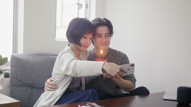 Young adult couple taking a selfie with japanese strawberry sponge cake on Christmas Video series of interracial couple making a morning pour over coffee, using technology, making internet payments with credit card and eating fried chicken and strawberry cake on Christmas. 20 29 years stock videos & royalty-free footage