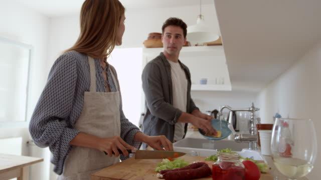 Jeune couple adulte parler comme ils préparent les aliments et laver vers le haut, tourné sur R3D - Vidéo