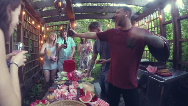 Jovem adulto comendo comida festa na piscina ao ar livre Summer BBQ - vídeo