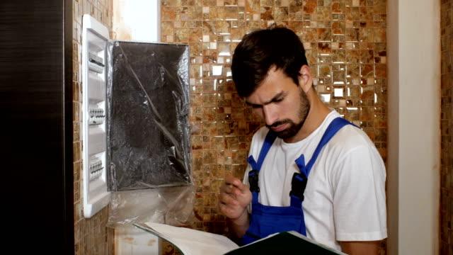 ヒューズ ボックスの機器をねじ込む若い大人電気技師ビルダー エンジニア - 電気工点の映像素材/bロール