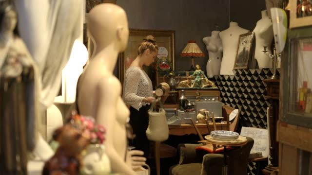 junge erwachsene weibliche charity-shop suchen - antique shop stock-videos und b-roll-filmmaterial