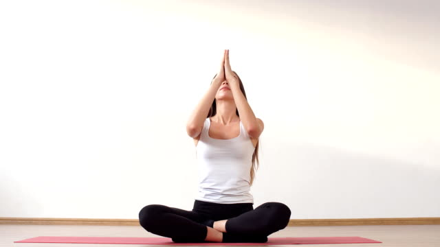 Young adult female doing yoga at home video