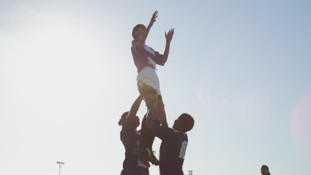 Young adult female rugby match Side view of a young adult mixed race female rugby player being lifted by two teammates to catch the ball and throwing it to a teammate during a rugby match rugby stock videos & royalty-free footage