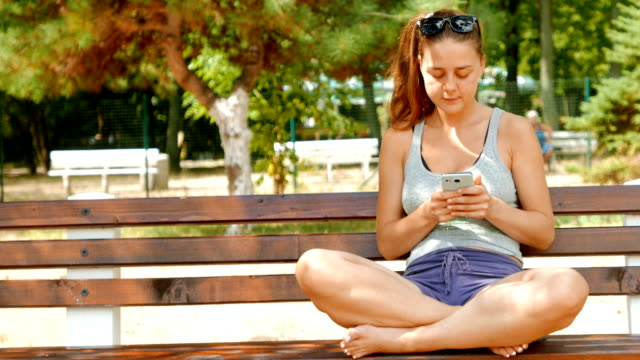 young adult female sitting on a bench in the park and using her smart phone - google стоковые видео и кадры b-roll