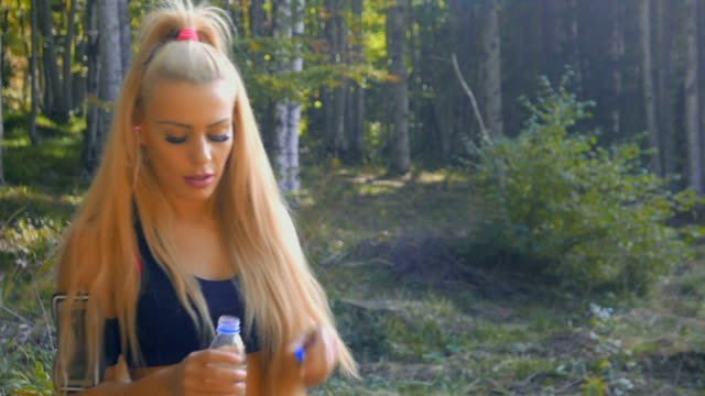 Young adult fitness girl resting from exercise and drinking water outdoors in the mountain forest video