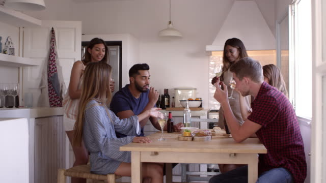 Young adult friends drinking and eating snacks in kitchen, shot on R3D video