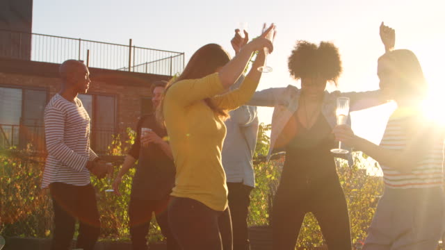 young adult friends having fun dancing at a rooftop party - generazione y video stock e b–roll