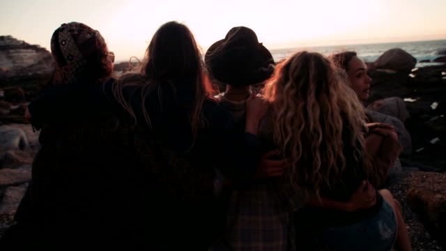 Young adult friends hugging on a sunset at the sea video