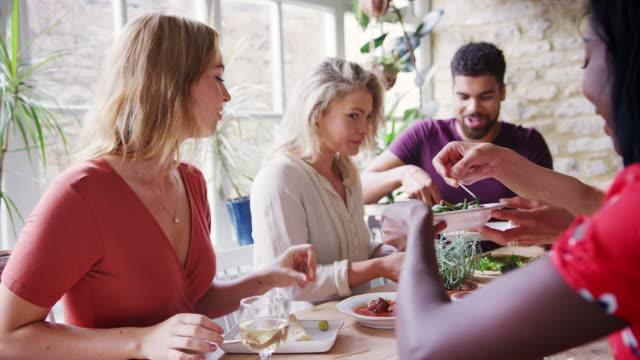 stockvideo's en b-roll-footage met jonge volwassen vrienden delen tapas gerechten voor de lunch in een restaurant tafel, selectieve aandacht - breakfast table