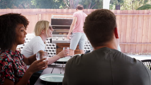 Young adult friends sitting outdoors barbecuing