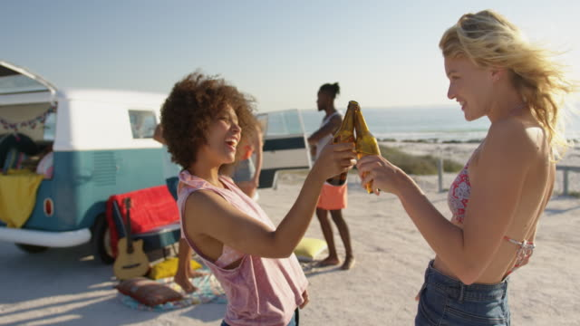 Young adult friends standing by a camper van at a beach 4k