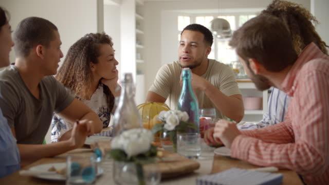 vidéos et rushes de jeunes adultes amis parler autour d'une table au cours du déjeuner, gros plan - diner entre amis