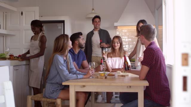 Jeunes adultes amis parler dans la cuisine faire un toast, abattu le R3D - Vidéo