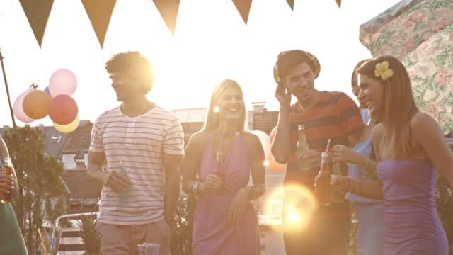 vidéos et rushes de jeunes adultes amis grillage à partie sur le toit - man drinking terrace