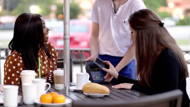 Young adult friends using contactless payment at outdoor cafe. video