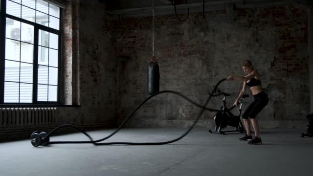 vídeos de stock, filmes e b-roll de jovem adulta praticando exercício de corda de batalha durante um treino de cross fit na academia - comodidades para lazer