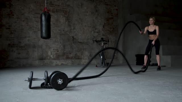 junge erwachsene mädchen üben kampf seil übung während eines cross-fit-training im fitnessstudio - religiöses symbol stock-videos und b-roll-filmmaterial
