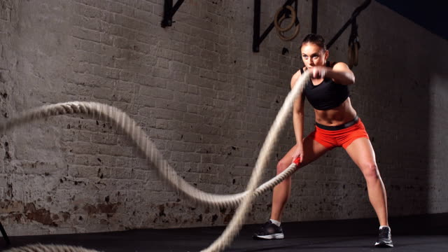 young adult girl practising battle rope exercise during a gym workout at the gym - битва стоковые видео и кадры b-roll
