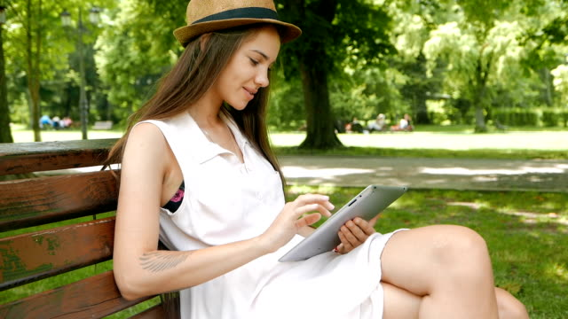 Young adult girl sitting on a bench outdoors and using a tablet video