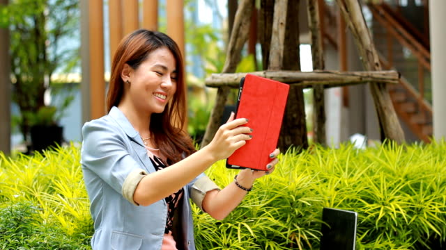 Young adult girl sitting on a bench outdoors and using a tablet facetime video