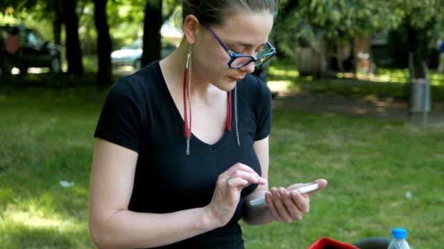 молодых взрослых девушка с использованием ее смартфон на свежем воздухе - google стоковые видео и кадры b-roll