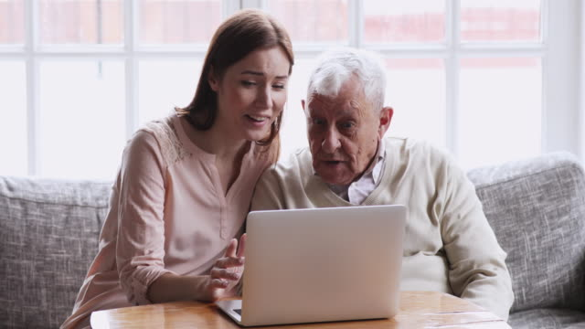 young adult grown granddaughter helping senior elder grandfather with computer - nipote femmina video stock e b–roll