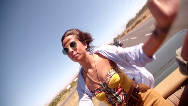 vídeos de stock e filmes b-roll de adultos jovens menina hippie com braços levantados em um carro descapotável - boho