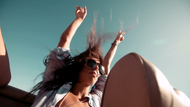 Young adult hippie girl with raised arms on a convertible car video