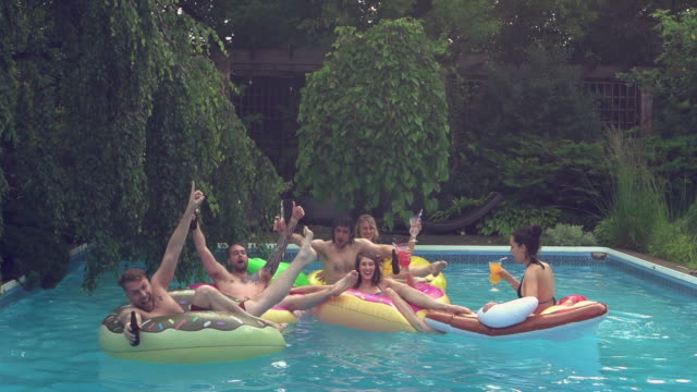 Jovens adultos pulando mergulho festa na piscina ao ar livre Summer BBQ - vídeo