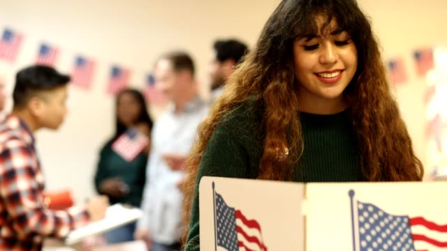 Young adult, Latin descent woman votes in USA election.