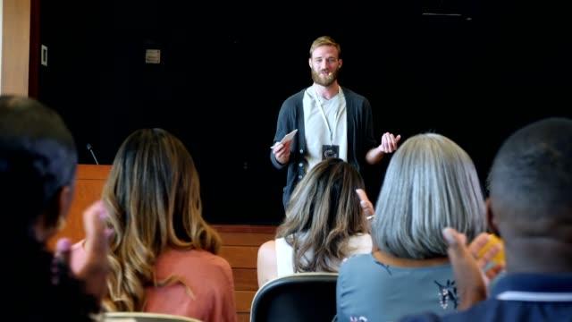 vídeos de stock e filmes b-roll de young adult male conference speaker talks to audience - orador público