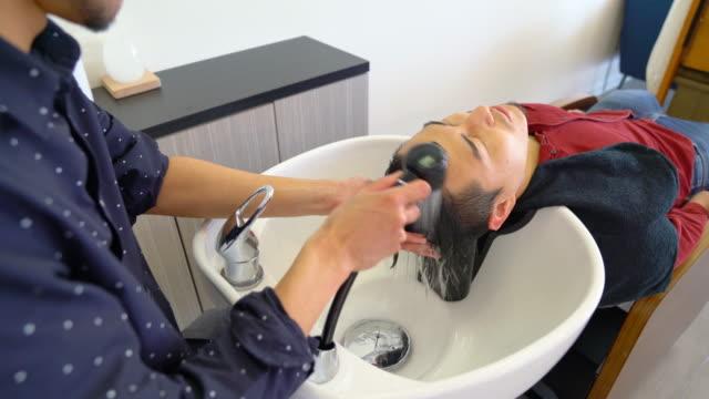 彼の髪をサロンで洗浄を取得若い成人男性 ビデオ