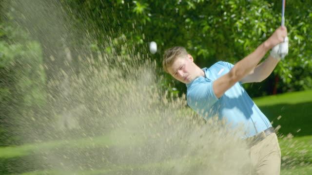 Ein junger erwachsener männlicher Golfer trifft einen Schuss aus einer Sandfalle, während sein Auge dem Ball folgt. – Video
