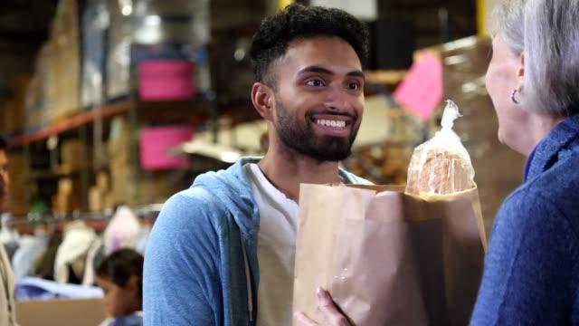 ung, vuxen hane händer papper påse med mat till mogen kvinna på en matbank - välgörenhet bildbanksvideor och videomaterial från bakom kulisserna