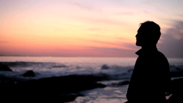 Young adult male staring across the ocean at sunset video
