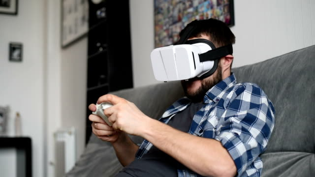 Young adult man and a virtual reality headset. Guy using vr glasses video