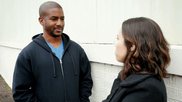 Young adult man and woman having discussion on city street video