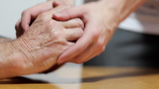 Young Adult Man Calming Senior Man's Hands Who Has Parkinson's Disease video
