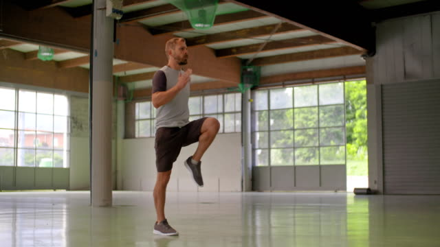 genç yetişkin adam yüksek diz egzersiz fitness spor egzersiz sırasında atlama yapıyor. grunge endüstriyel kentsel training.4k ağır çekim video - uzun fiziksel özellikler stok videoları ve detay görüntü çekimi