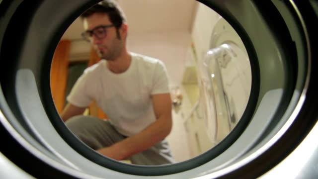 vídeos de stock, filmes e b-roll de jovem adulto homem fazendo lavanderia - afazeres domésticos