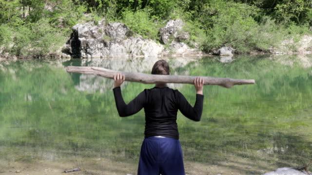 ung vuxen man utövar med trädstam på riverbank - rådig bildbanksvideor och videomaterial från bakom kulisserna