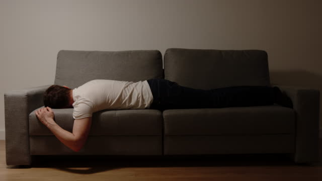 DEPRESSION: Young adult man lies on sofa in the night video