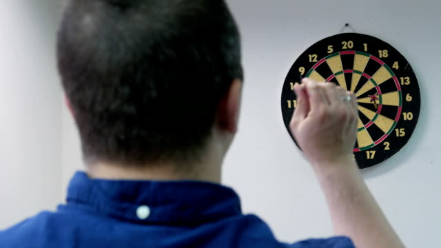 Young adult man playing darts in the office video