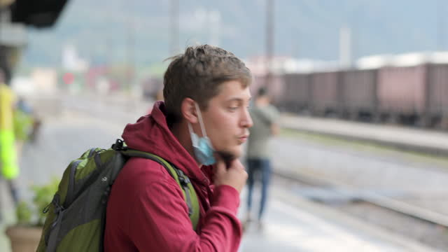Young Adult Man Putting on Protective Face Mask Before Entering Train video