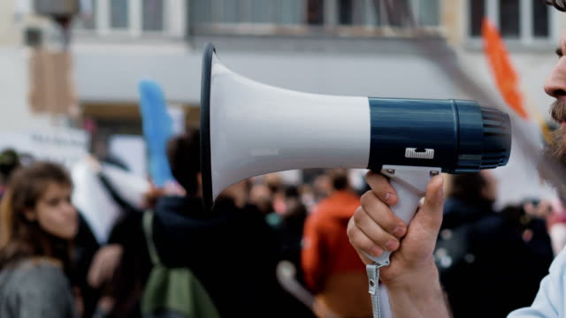 Young adult man shouts in megaphone. Caucasian people shout violently and angry. A desperate man goes and demands a megaphone on strike. European guy with a beard is yelling into the loudspeaker at a rally. People are unhappy with the government. Revolution on the street in city. megaphone stock videos & royalty-free footage