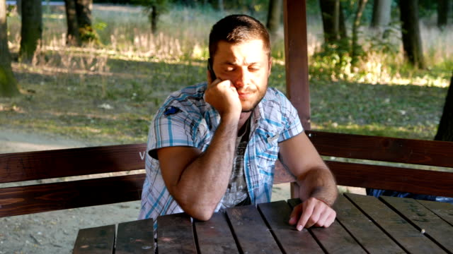 Young adult man sitting in the park and talking on the phone video