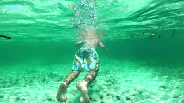 Young Adult Man Snorkeling and Exploring Ocean Floor
