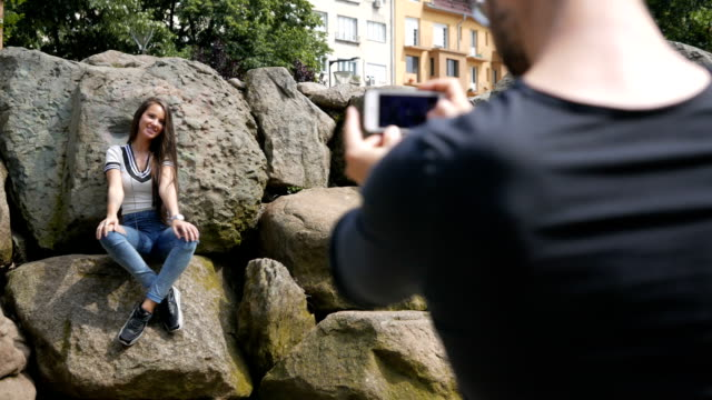 Young adult man takes pictures of his girl friend using a smart phone Medium to close up rear view shot of a young adult boy who takes pictures of his girl friend using a smart phone. The girl is posing while standing over some rocks. Both the male and the female are attractive and casually dressed. The scene is situated outdoors in a city park during the day. The footage is taken with Panasonic Lumix LX-100 camera. heterosexual couple stock videos & royalty-free footage