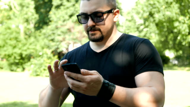 Young adult man using his smart phone outdoors video